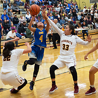 Kaitlyn Romencito (4) of Zuni draws the foul and scores on the play with Rehoboth defenders in the paint in Rehoboth on Saturday. Zuni won 48-37.