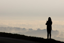 © Licensed to London News Pictures. 22/11/2018. Dorking, UK. A woman stops to take a phone photo from Box Hill near Dorking as mist and frost cover the valley below. Photo credit: Peter Macdiarmid/LNP