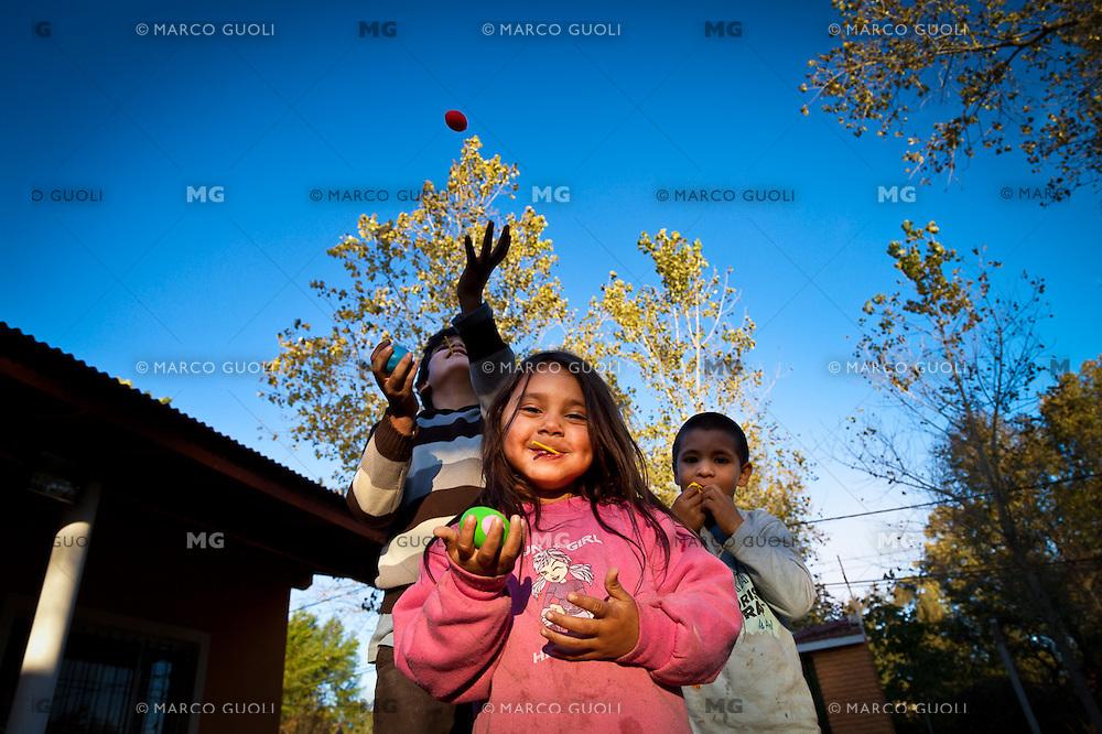 """NINOS DE LA CLASE DE """"APOYO ESCOLAR DULCE ESPERANZA"""" JUEGAN EN EL JARDIN DEL COMEDOR """"TODOS JUNTOS"""", DIQUE LUJAN, PROVINCIA DE BUENOS AIRES, ARGENTINA (PHOTO © MARCO GUOLI - ALL RIGHTS RESERVED)"""