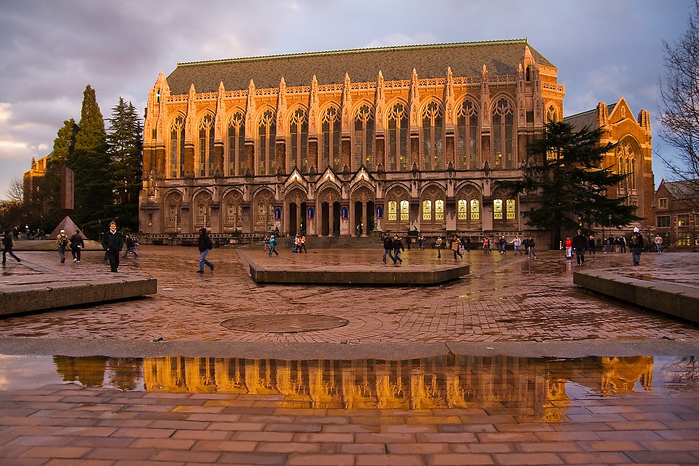 The neo-gothic Suzzallo Library is reflected by water on the bricks of Red Square at the University of Washington in Seattle, Washington.