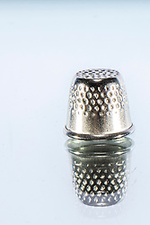Silver colored sewing thimble on white background