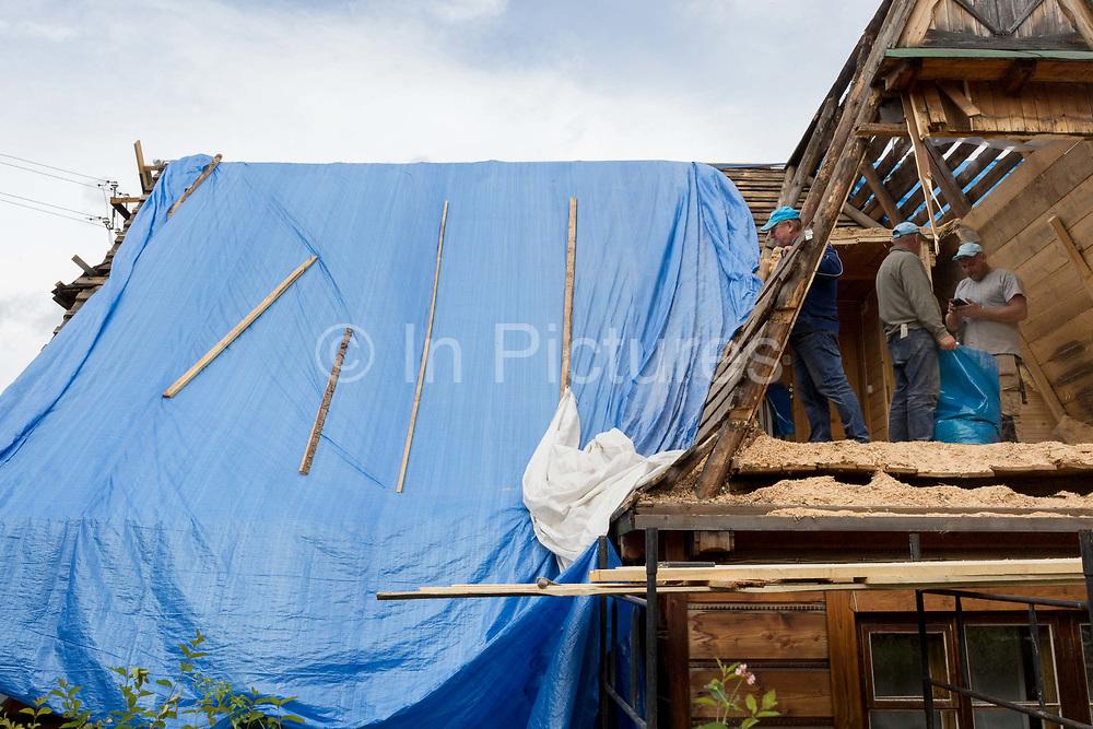 Workmen repair the timbers of a traditional Polish mountain houses gable roof, on 16th September 2019, in Zakopane, Malopolska, Poland.