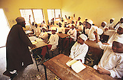 Islamic school for boys and youths in Kano..The implementation of Islamic Sharia Law across the twelve northern states of Nigeria, centres upon Kano, the largest Muslim Husa city, under the feudal, political and economic rule of the Emir of Kano. Islamic Sharia Law is enforced by official state apparatus including military and police, Islamic schools and education, plus various volunteer Militia groups supported financially and politically by the Emir and other business and political bodies. Fanatical Islamic Sharia religious traditions  are enforced by the Hispah Sharia police. Deliquancy is controlled by the Vigilantes volunteer Militia. Activities such as Animist Pagan Voodoo ceremonies, playing music, drinking and gambling, normally outlawed under Sharia law exist as many parts of the rural and urban areas are controlled by local Mafia, ghetto gangs and rural hunters. The fight for control is never ending between the Emir, government forces, the Mafia and independent militias and gangs. This is fueled by rising petrol costs, and that 70% of the population live below the poverty line. Kano, Kano State, Northern Nigeria, Africa