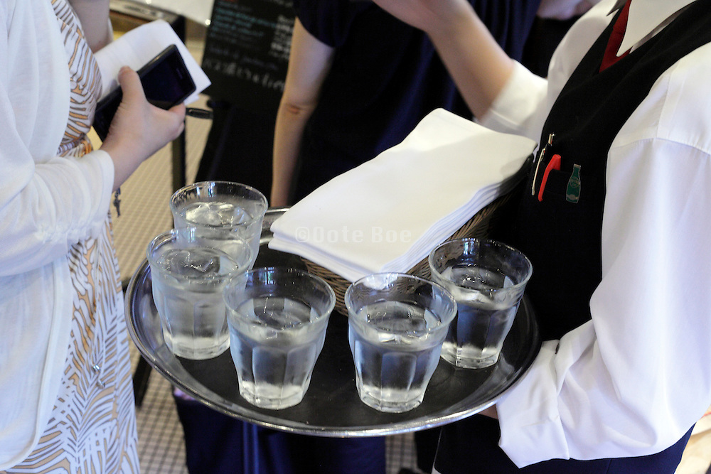 waitress with glasses cold water on serving tray