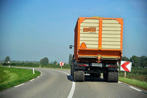 Nederland, Kekerdom, 30-9-2011Een tractor met aanhanger rijdt op de dijk, gezien vanuit  een personenauto. De weg is te smal om hem te passeren. Het is oogsttijd voor de mais waardoor er veel klei op het wegdek komt en de binnenwegen glad kunnen wordenFoto: Flip Franssen/Hollandse Hoogte