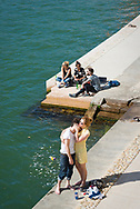 Young adults enjoy a summer day beside the Saône River in Lyon, France