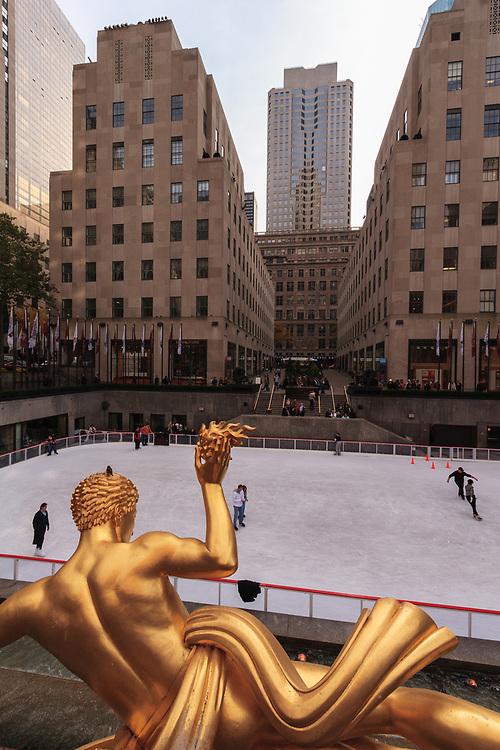 Golden statue of Prometheus in Rockefeller Center. The Rockefeller Center skating rink is guarded by the famous gilded statue of Prometheus who brings fire to mankind by sculptor Paul Manship.