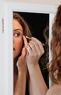 Beautiful woman's reflection in a bathroom mirror, putting on eyeliner.