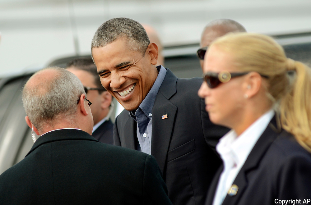 President Barack Obama laughs with an acquintance while making his way through a small crowd upon his arrival to the Buffalo Niagara International Airport, Thursday, August 22, 2013. (AP <br /> Photos/Heather Ainsworth)
