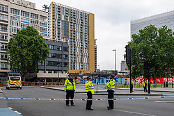 """© Licensed to London News Pictures. 28/06/2021. London, UK. Metropolitan Police officers maintain a large cordon. One hundred firefighters tackled a fire near Elephant and Castle railway station in southeast London. London Fire Brigade (LFB) said three commercial units in railway arches were """"completely alight"""", in addition to six cars and a telephone box. Photo credit: Peter Manning/LNP"""