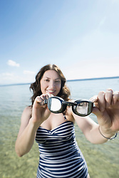 Mature woman holding swimming goggles and smiling at lake, Bavaria, Germany
