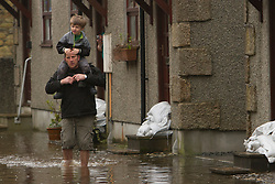 © Licensed to London News Pictures. 22/12/2012. Helston, UK. A man carries a child through flood water in Helston caused by the River Cober bursting its banks over night after heavy rain across the South West. The Environment Agency issued a Severe flood warning for the River Cober. Photo credit : Ashley Hugo/LNP