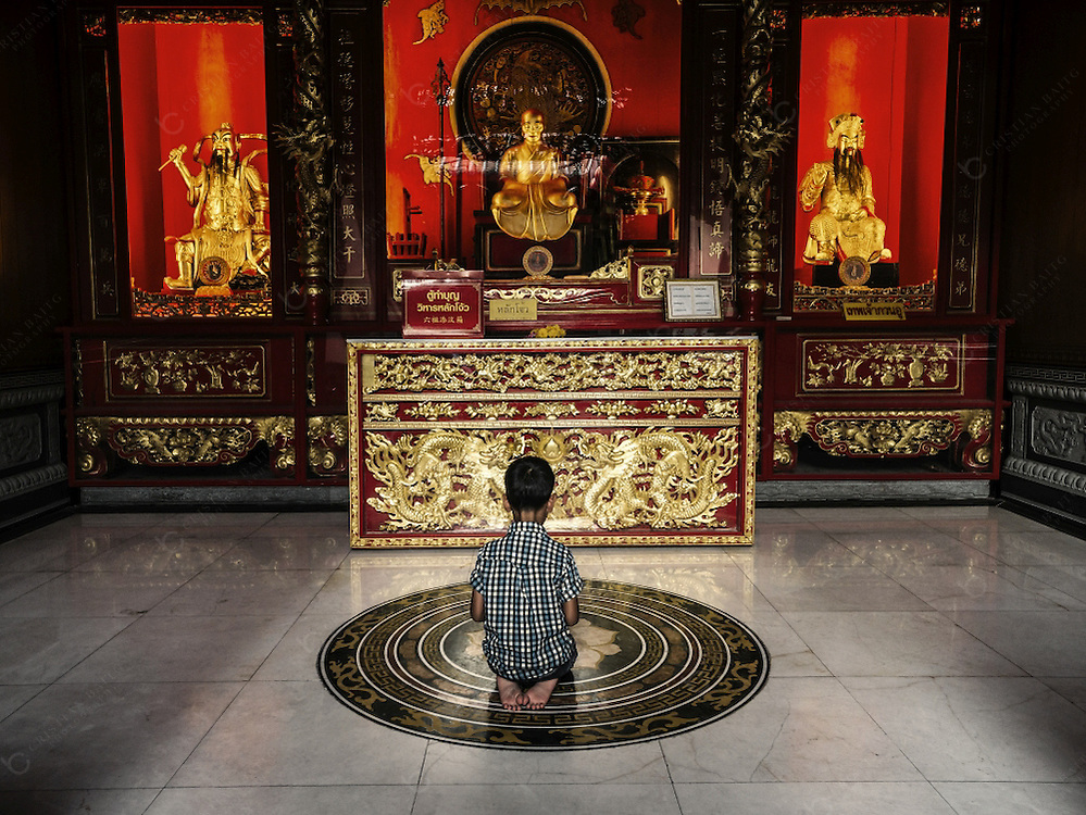 Child praying at Wat Mangkol Kamalawat temple Bangkok Thailand. It is the most important and revered temple in Chinatown. The temple contains Buddhist, Taoist, and Confucian deities.