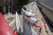 A City of London Griffin looks over Farringdon Road, London. With its red eye and tongue almost touching two pedestrians below, we see its silver-painted skin Positioned at the boundary of what is called the Square Mile, the griffins are symbols of this ancient area of central London, a semi-autominous geographically-small City within Greater London, England. The City of London is the historic core of London from which, along with Westminster, its more modern conurbation grew. The City's boundaries have remained constant since the Middle Ages but  it is now only a tiny part of Greater London, approximately one square mile (2.6 km) in area. London Bridge's history stretches back to the first crossing over Roman Londinium.