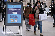 On the day that the UK government eased Covid restrictions to allow non-essential businesses such as shops, pubs, bars, gyms and hairdressers to re-open, shoppers walk past Next's board displaying the maximum number of customers allowed inside the Oxford Street shop, on 12th April 2021, in London, England.