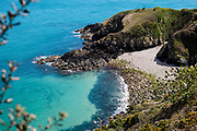 Hidden bay Vicard Harbour on a Spring day in Jersey, CI - surrounded by calm clear turquoise water, the headland and cliffs