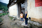Young children play in front of a home in the village of Duntang, in Daoxian County, Hunan Province, China, on 03 June, 2010. Duntang was connected to the main electricity grid and began to receive regular supply of electricity only since the beginning of 2009.