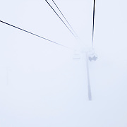 Snow and wind decrease visibility on a lift at Mammoth Mountain.