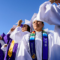 Danielle Miller, center, and her classmates turn to look for their families in the crowd as the Miyamura High School graduates take their seats for the commencement ceremony Friday at Public School Stadium in Gallup.