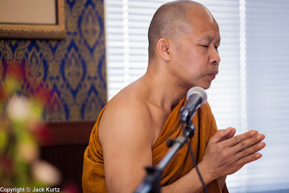 """11 MARCH 2012 - CHANDLER, AZ:   The Abbot leads a chanting service in the """"bot"""" or ordination hall during Makha Bucha Day services at Wat Pa in Chandler, AZ, Sunday. Magha Puja (also spelled Makha Bucha) Day marks the day 2,500 years ago that 1,250 Sangha came spontaneously to see the Buddha who preached to them on the full moon. All of them were """"Arhantas"""" or Enlightened Ones who had been personally ordained by the Buddha. The Buddha gave them the principles of Buddhism, called """"The Ovadhapatimokha."""" Those principles are: to cease from all evil, to do what is good, and to cleanse one's mind. It is one of the most important holy days in the Theravada Buddhist tradition. At the temple, people participate in the """"Tum Boon"""" (making merit by listening to the monk's preaching and giving a donation to the temple), the """"Rub Sil"""" (keeping of the Five Precepts including the abstinence from alcohol and other immoral acts) and the """"Tuk Bard"""" (offering food to the monks in their alms bowls). It is a day for veneration of the Buddha and his teachings. It's a legal holiday in Thailand, Laos, Cambodia and Myanmar (Burma).       PHOTO BY JACK KURTZ"""