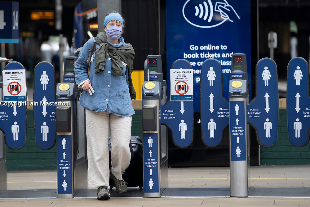 Edinburgh, Scotland, UK. 22 June, 2020. From today it is mandatory for passengers to wear face coverings when travelling on railways and public transport in Scotland. Staff at Waverley Station in Edinburgh are handing out free face masks and hand sanitiser to passengers. Iain Masterton/Alamy Live News