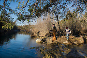 Camron Hanks casts for trout while his son Lane plays in the background.  Blue River near Tishomingo, Oklahoma