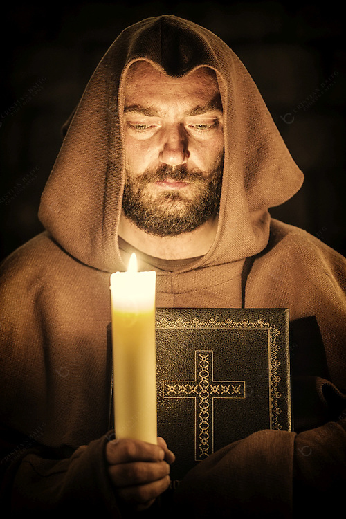 Monk holding lit candle and the Bible