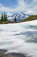 Mount Shuksan seen from partially thawed tarn, Yellow Aster Butte Basin, Mount Baker Wilderness, North Cascades Washington