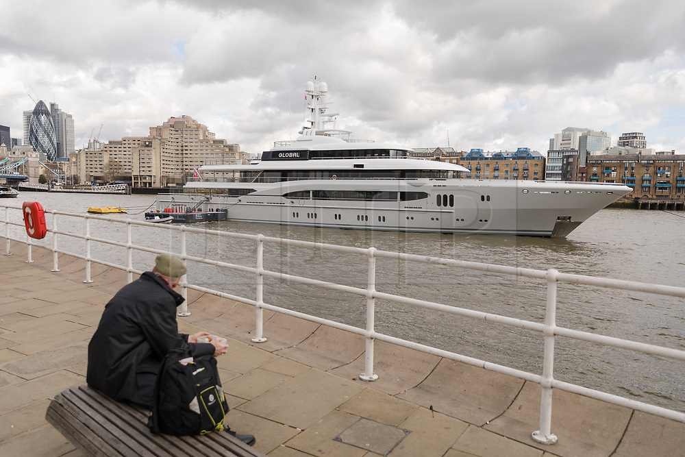 © Licensed to London News Pictures. 29/03/2018. London, UK. A man looks at the 220ft custom luxury superyacht, 'Global' moored at Butlers Wharf near Tower Bridge during a London visit. Previously named, Kismet during her last central London visit, she underwent a refit which saw her moved up 51 places in Boat International's list of top 200 largest super yachts in the world, boasting numerous luxuries such as a helipad, cinema and jacuzzi. Believed to be owned by Fulham Football Club chairman, Shahid Khan, Global can be chartered for an estimated £1m per week. Powered by 2 Caterpillar (3512 B) 2,038hp diesel engines and propelled by her twin screws propellers, Global is capable of a top speed of 15.5 knots, and comfortably cruises at 14 knots.. Photo credit: Vickie Flores/LNP