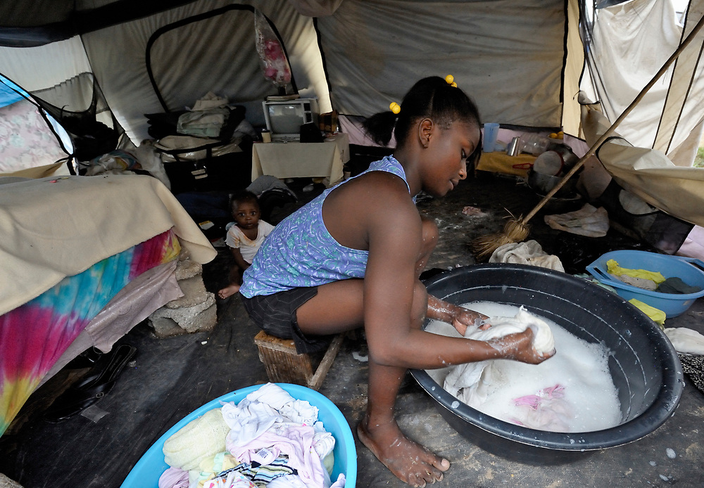 """A woman washes laundry inside her shelter in a """"tent city"""" of homeless earthquake survivors in the Bobin neighborhood of Port-au-Prince, Haiti. The January 2010 earthquake ravaged the capital, killing some 300,000 people and leaving more than 1.3 million homeless."""