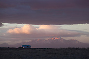 Storm clouds pass over a parked RV trailer at sunrise near the San Rafael Swell, Utah, with the Henry Mountains in the background.