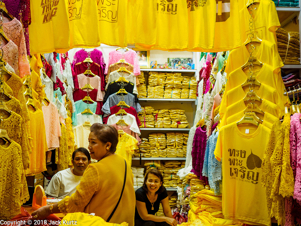 """03 JULY 2018 - BANGKOK, THAILAND: A shop that sells yellow tee shirts that say """"Long Live the King"""" in Bobae Market in Bangkok. The birthday of King Maha Vajiralongkorn Bodindradebayavarangkun, Rama X, is 28 July. The King, the only son of Thailand's late King Bhumibol Adulyadej, became the King of Thailand in 2016 after the death of his father. King Vajiralongkorn was born on 28 July 1952, a Monday. In Thai culture each day of the week has a color, and yellow is the color is associated with Monday, so people wear yellow for the month before his birthday to honor His Majesty.    PHOTO BY JACK KURTZ"""