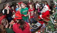 Emma Wheeler, Mollie Durand and Laura Schwarz await their presents from Santa Elves at the Wicwas Grange Christmas party for family and friends.  (Karen Bobotas/for the Laconia Daily Sun)