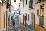 Young woman in casual clothes walking in cobble street passing typical white and yellow houses in Evora, Portugal