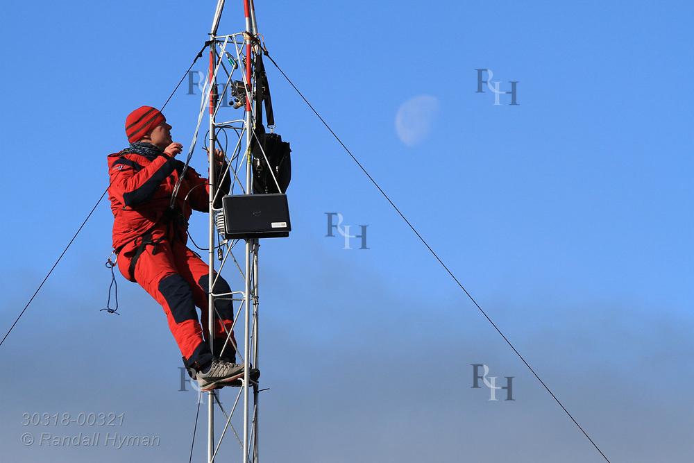 Technician works on radio tower on shore of Rijpfjorden on Nordaustlandet in late July; Svalbard, Norway.