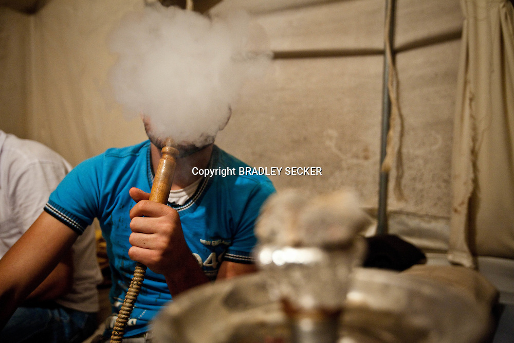 A Syrian refugee smokes a water pipe in Yayladagi refugee camp, Hatay, southern Turkey. The number of refugees fleeing from Idlib province in neighbouring Syria has reached more than 20,000 according to the Turkish government. 07/07/2012