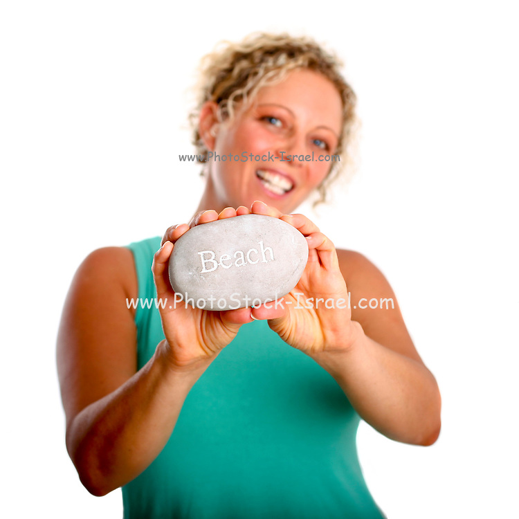 Young woman holds a pebble with BEACH written on it as a request to save and protect our beaches