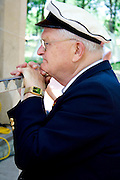 Man age 80 wears cap and jacket uniform of Sweden Svenskarnas Dag Swedish Heritage Day Minnehaha Park Minneapolis Minnesota USA