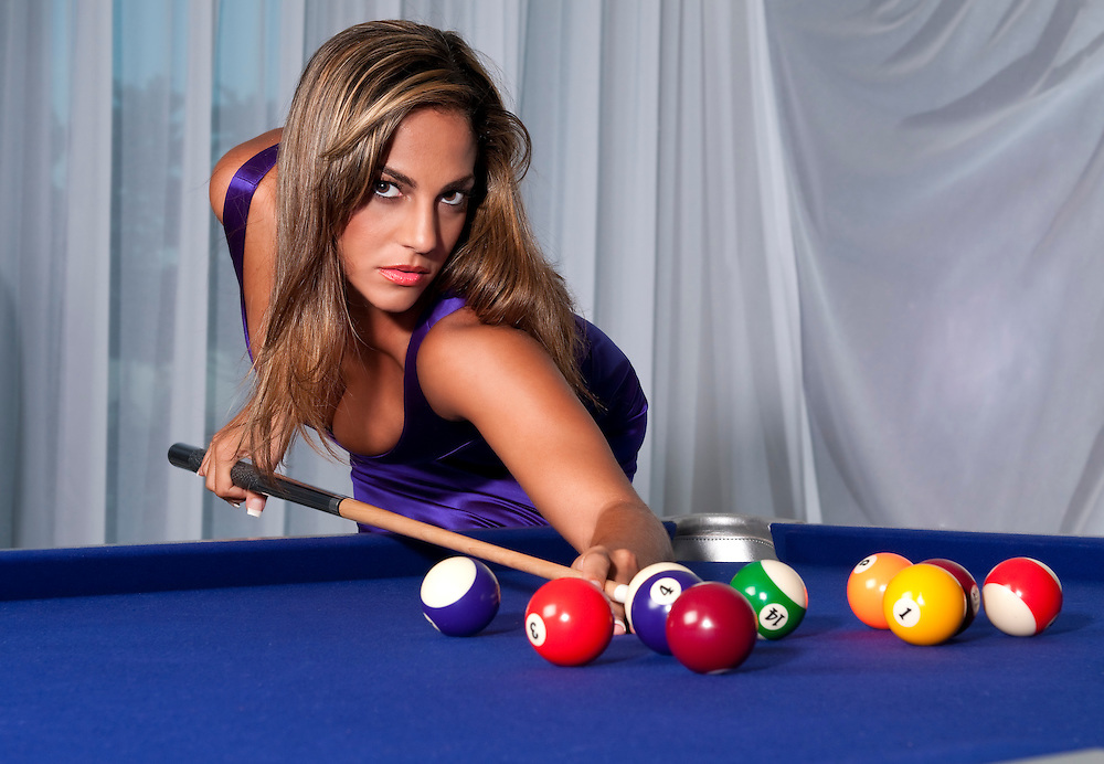 Young hispanic girls plays pool with a very sexy dress.