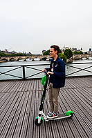A French teenager rides an electric scooter across the pedestrian Pont des Arts (bridge) , Paris, France.