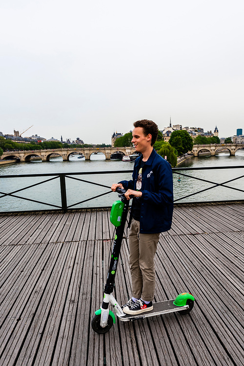 A French teenager rides an electric scooter across the pedestrian Pont des Arts (bridge) , Paris, France.