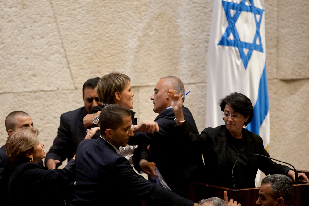 Arab-Israeli lawmaker MK Hanin Zoabi (R), who was on board the Gaza-bound flotilla when it was raided by Israeli forces, speaks at the Israeli parliament, as Israeli lawmaker MK Anastassia Michael (L), of the right-wing Yisrael Beteinu party, shouts at her and is escorted off of the podium at the Knesset in Jerusalem, Israel, on June 2, 2010.