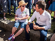 13 AUGUST 2019 - DES MOINES, IOWA: PATTY JUDGE, former Lt. Governor of Iowa, talks to PETE BUTTIGIEG while he eats a pork chop on a stick at the Iowa State Fair. Buttigieg, the Mayor of South Bend, Indiana, is running to be the Democratic nominee for the US presidency. He spoke at the Des Moines Register Political Soap Box at the Iowa State Fair and then toured the fairgrounds. Iowa has the first event of the presidential selection cycle. The Iowa Caucuses are February 3, 2020.               PHOTO BY JACK KURTZ