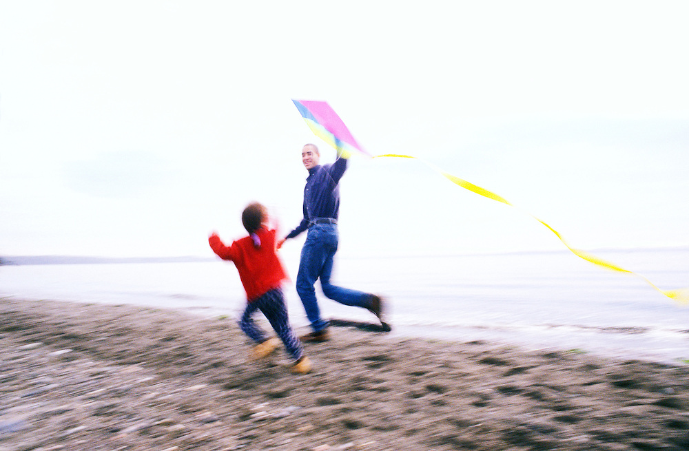A father and daughter running and flying a kite on a rocky beach.