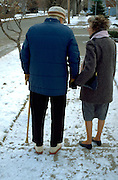 Retired physician age 87 and wife age 73 walking near their home.  Minneapolis  Minnesota USA