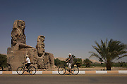 Tourists on rented bikes cycle past the ancient Egyptian Colossi of Memnon site, Luxor, Nile Valley, Egypt. The Colossi of Memnon (memorial temple of Amenophis III) are two massive stone statues of Pharaoh Amenhotep III, who reigned during Dynasty XVIII. For the past 3,400 years (since 1350 BC) they have stood in the Theban necropolis, west of the River Nile from the modern city of Luxor.
