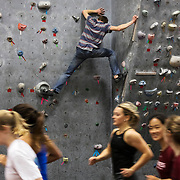 Sam Onion '20 of Wayne, Maine, geology major, trains on the rock wall in Merrill Gymnasium as the men's and women's track and field team is seen running along the indoor track.