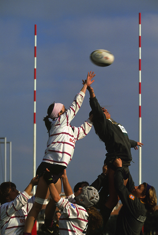 Two girls disputing a line out during a Loule vs. Agraria de Coimbra match. Their team mates help them to jump to win the ball for their sides.