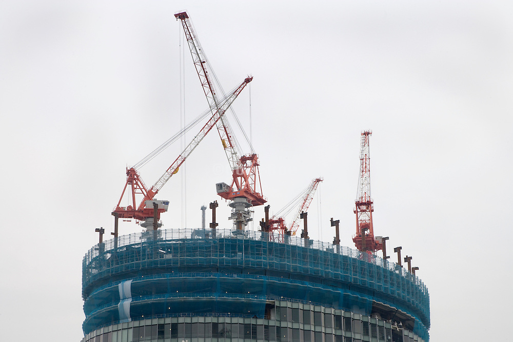 building of a very big high rise with various cranes on top