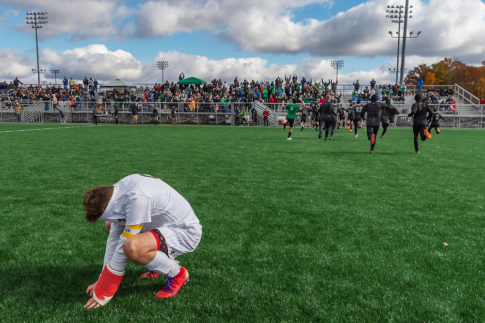 East Fairmont's team captain Corey Fluharty hides his face in his shirt as Winfield celebrates their victory during the Winfield-East Fairmont AA-A boys State soccer championships at the YMCA Paul Cline Memorial Youth Sports Complex in Beckley, W.Va., on November 03, 2018.
